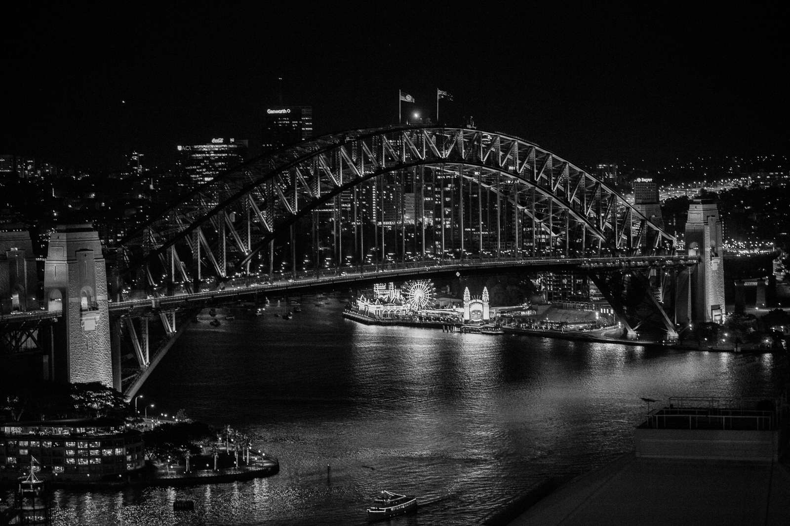 Black-and-white Sydney Harbour Bridge and Luna Park at night